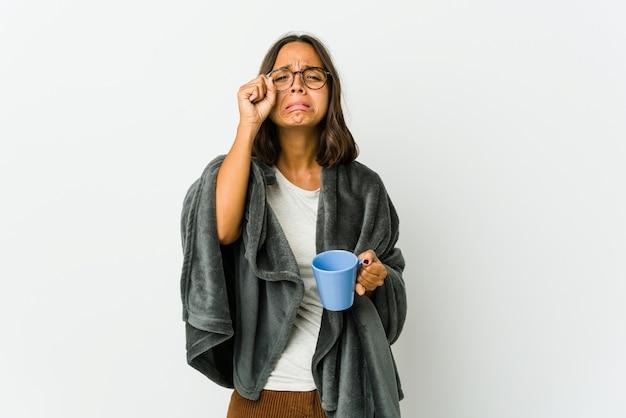 Молодая латинская женщина с одеялом, изолированным на белой стене, безутешно плачет и плачет.