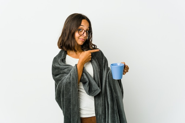 Young latin woman with blanket isolated on white background pointing with forefingers to a copy space, expressing excitement and desire.