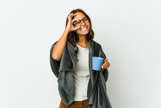 Young latin woman with blanket isolated on white excited keeping ok gesture on eye.