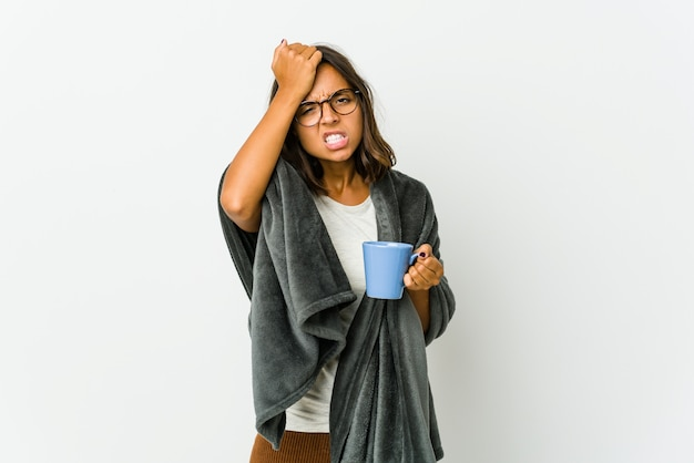 Young latin woman with blanket isolated on white forgetting something, slapping forehead with palm and closing eyes.
