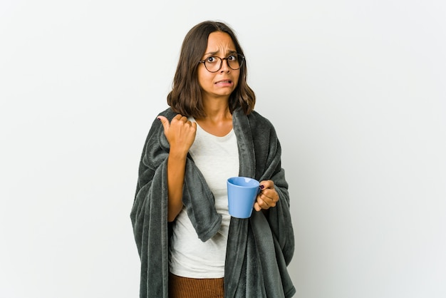 Young latin woman with blanket isolated on white shocked pointing with index fingers to a copy space.