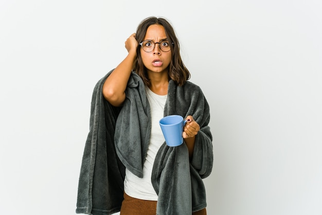 Young latin woman with blanket isolated on white wall covering ears with hands trying not to hear too loud sound.