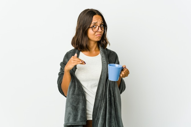 Young latin woman with blanket isolated on white wall showing a timeout gesture.