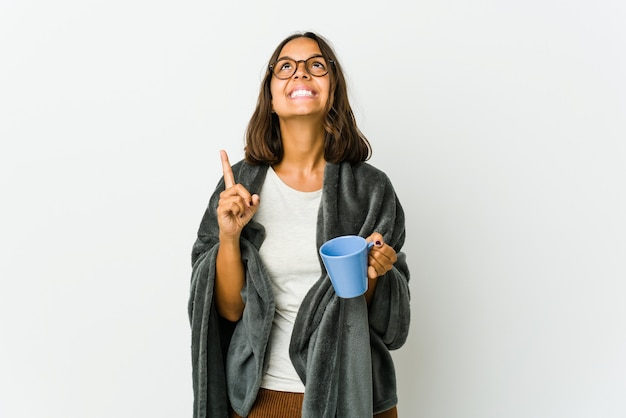 Young latin woman with blanket isolated