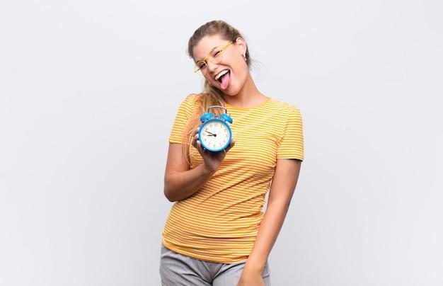 Молодая латинская женщина с веселым, беззаботным, бунтарским настроем, шутит и высунула язык, развлекается с будильником