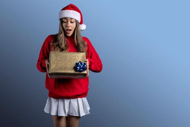 彼女の手とテキストのためのスペースに贈り物を持ったクリスマスの服を着た若いラテン女性