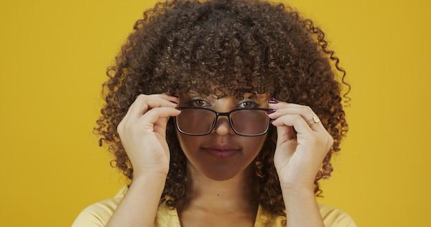 彼女の眼鏡に満足している巻き毛の若いラテン女性。アイケアのコンセプト。