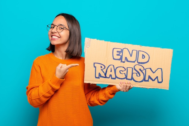 Young latin woman with end racism board