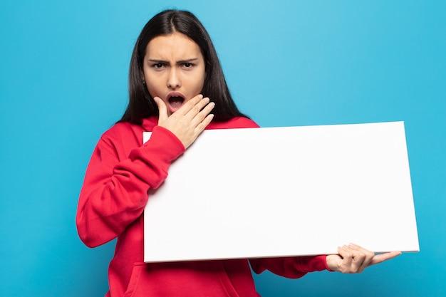 Молодая латинская женщина с широко открытыми глазами и ртом, положив руку на подбородок, ощущает неприятный шок, говорит что или вау