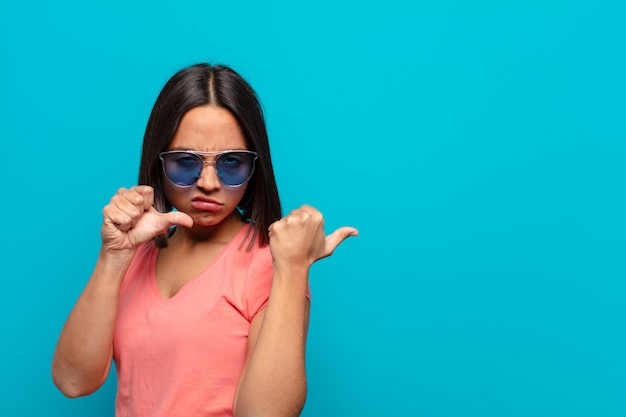 Young latin woman with sun glasses and a copy space