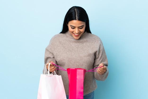 쇼핑백을 들고 내부를 찾고 파란색 벽에 젊은 라틴 여자 여자