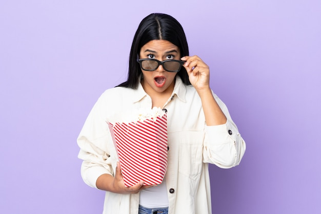 Young latin woman woman on white wall surprised with 3d glasses and holding a big bucket of popcorns