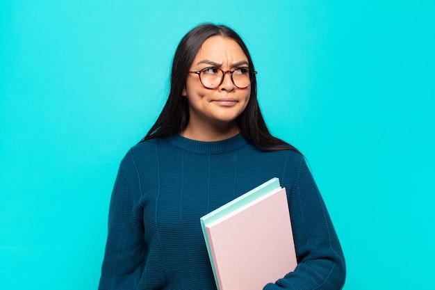 Молодая латинская женщина задается вопросом, думает о счастливых мыслях и идеях, мечтает, ищет, чтобы скопировать пространство на стороне