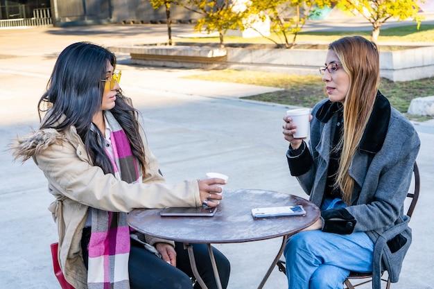 화창한 날 야외 카페에서 커피를 마시는 젊은 라틴 여성.
