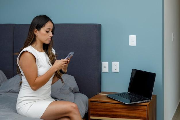 彼女のアパートの寝室で彼女のラップトップに取り組んでいる若いラティーナの実業家