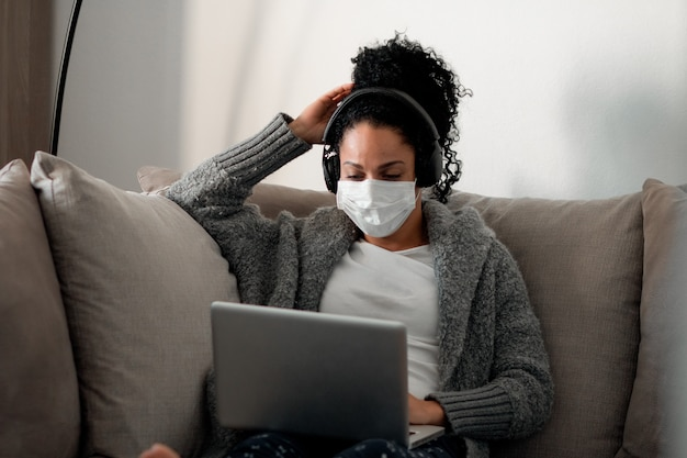 Young latina female with a medical mask working from home during the coronavirus pandemic