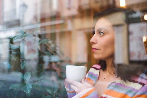 Young latina looking through the window of a coffee shop with reflections while drinking a cup of coffee