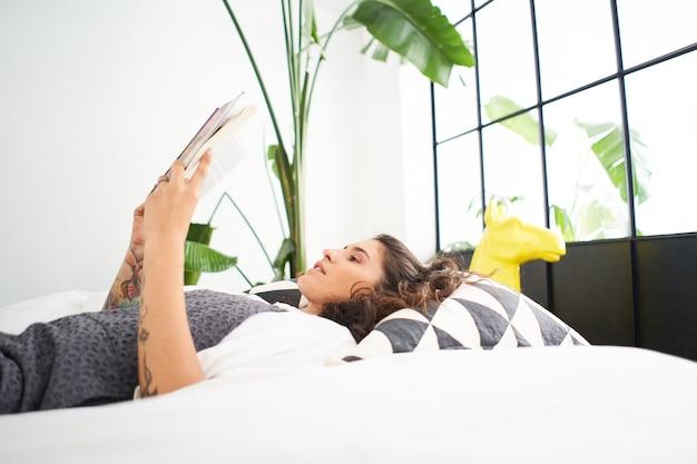 집에서 공부하고 배우는 침대에 누워 책을 읽는 젊은 라티나 여성