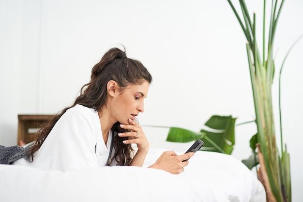 Молодая латинская женщина с помощью мобильного телефона, лежа на кровати, люди подключались из дома во время расслабления ...