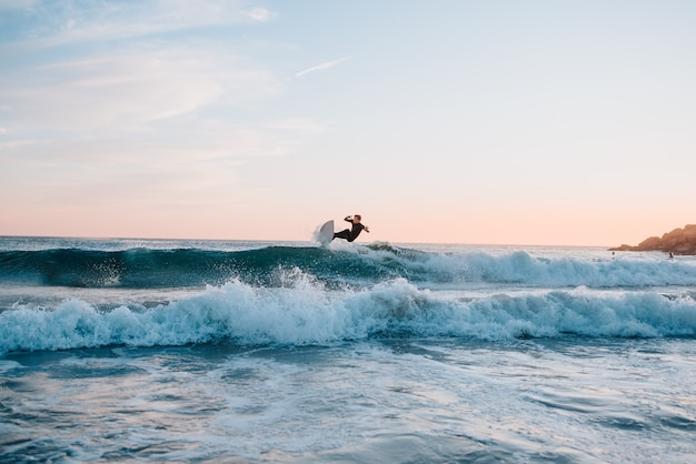 Young latino boy doing surf tricks while catching the waves at sunset. copy space