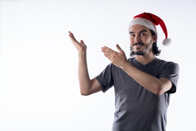 サンタクロースの帽子をかぶったラテン系の若者。笑顔で両手を横に見せています。白色の背景