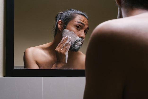 헤어 리본을 착용 한 젊은 라틴계 남자가 화장실에 면도 거품을 넣습니다.