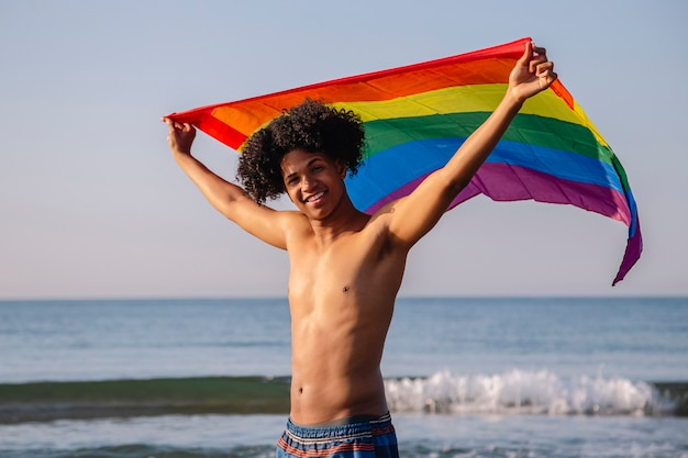 Lgtbi 깃발을 보여주는 아프리카 머리를 가진 젊은 라틴계 남자