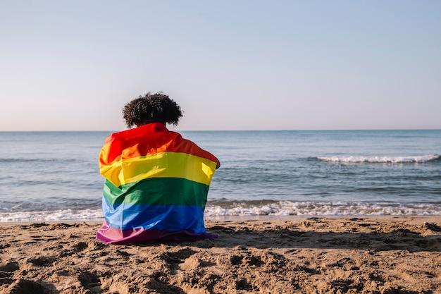아프리카 머리를 가진 젊은 라틴계 남자가 lgtbi 깃발을 들고 해변에 앉아 있다
