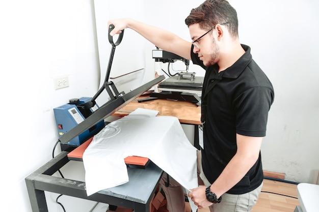 젊은 라틴계 남자는 티셔츠 승화 기계를 사용합니다.