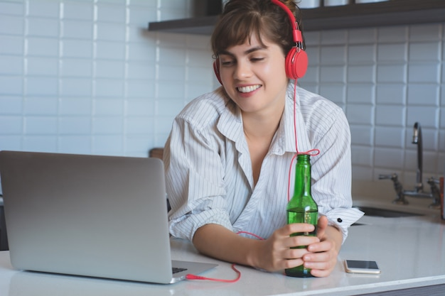 Young latn woman with beer and using her laptop pc