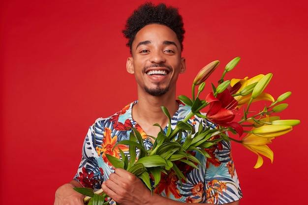 Giovane uomo afroamericano che ride, indossa in camicia hawaiana, guarda la telecamera con espressione felice, detiene bouquet di fiori gialli e rossi, si erge su sfondo rosso.