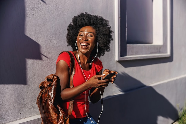 Young laughing african woman standing outdoors, holding smart phone and listening music.