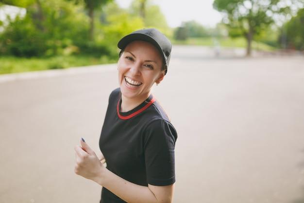 Giovane bella ragazza bruna atletica ridente in uniforme nera e allenamento con berretto facendo esercizi sportivi in esecuzione e guardando la telecamera sul percorso nel parco cittadino all'aperto