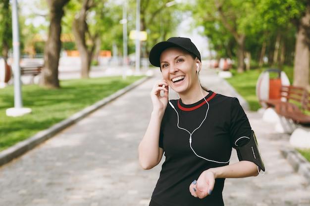 야외 도시 공원에서 훈련에 귀 근처에 손을 유지, 음악을 듣고 이어폰으로 검은 색 유니폼과 모자에 젊은 웃음 운동 아름 다운 갈색 머리 여자