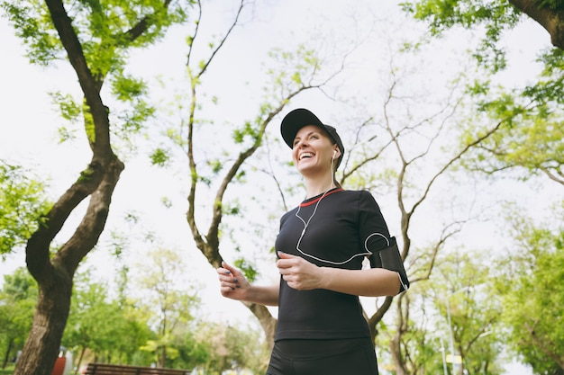 Young laughing athletic brunette woman in black uniform and cap with earphones training doing sport, running and listening to music on path in city park outdoors