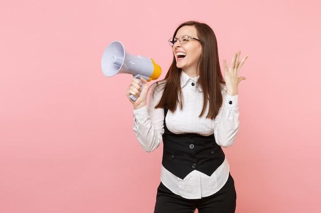 Молодой смеясь над привлекательной деловой женщиной в черном костюме, рубашке в очках, держа мегафон, раздвигая руки, изолированные на розовом фоне. леди босс. достижение карьерного богатства. скопируйте место для рекламы.