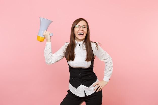 Молодая смеющаяся красивая деловая женщина в черном костюме и очках, держащая мегафон, изолирована на пастельно-розовом фоне. леди босс. концепция богатства карьеры достижения. скопируйте место для рекламы.