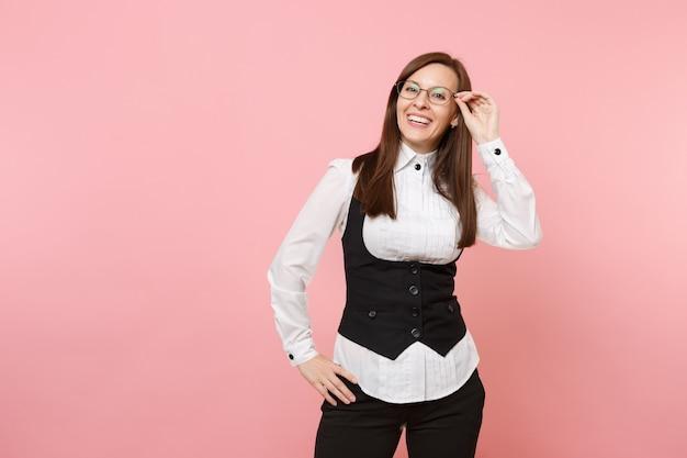 파스텔 핑크 배경에 격리된 안경을 들고 검은 양복과 흰색 셔츠를 입은 젊은 웃고 있는 아름다운 비즈니스 여성. 여사장님. 성취 경력 부 개념입니다. 광고 공간을 복사합니다.