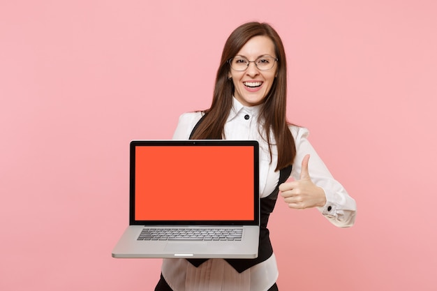 Young laughing business woman in glasses hold laptop computer with blank empty screen showing thumb up isolated on pink background. lady boss. achievement career wealth. copy space for advertisement.