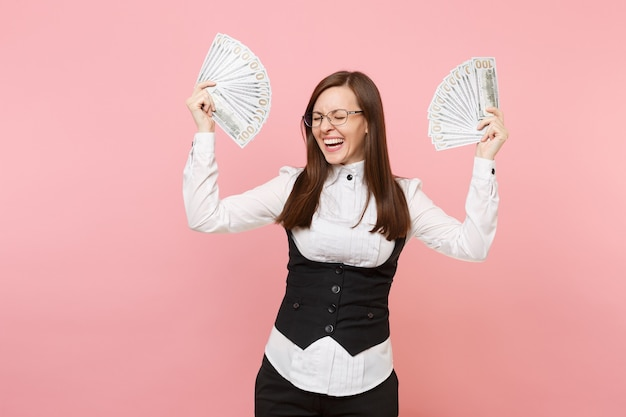 Young laughing business woman in glasses holding bundle lots of dollars, cash money and spreading hands isolated on pink background. lady boss. achievement career wealth. copy space for advertisement.