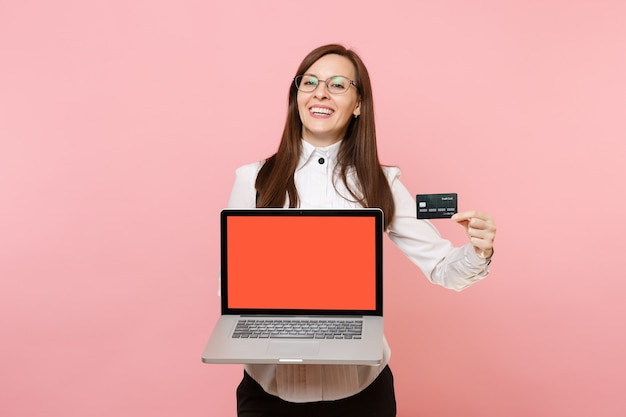 Young laughing business woman in glasses holding credit card laptop pc computer with blank empty screen isolated on pink background. lady boss. achievement career wealth. copy space for advertisement.