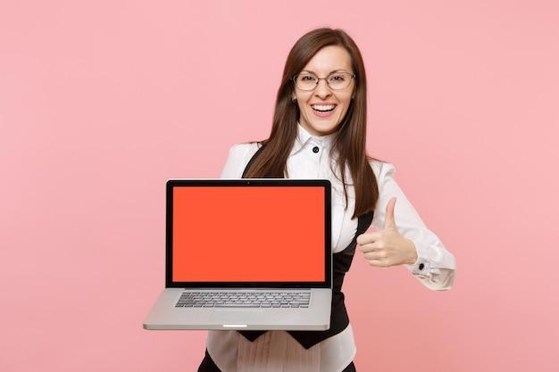 안경을 쓴 젊은 웃고 있는 비즈니스 여성은 분홍색 배경에 고립된 엄지손가락을 보여주는 빈 화면이 있는 노트북 컴퓨터를 들고 있습니다. 여사장님. 성취 경력 부입니다. 광고 공간을 복사합니다.