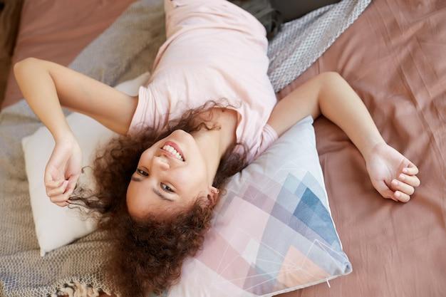 젊은 웃음 어두운 피부 젊은 아가씨, 침대에 누워, 넓게 웃고 행복해 보이며 화창한 날을 집에서 즐기십시오.