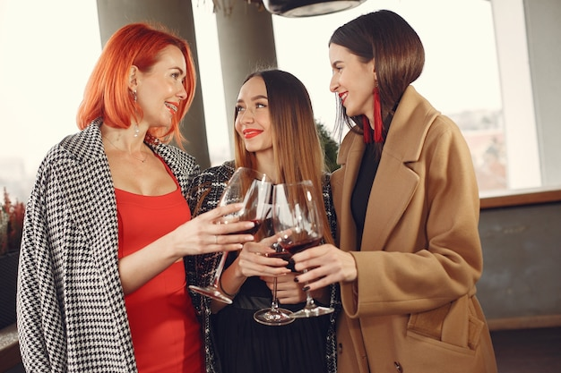 外のガラスからロゼワインを飲む若い笑い友達
