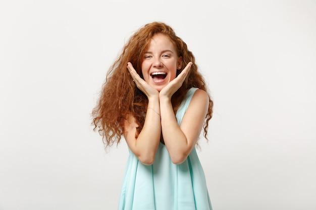 スタジオで白い背景に分離されたポーズをとってカジュアルな明るい服を着た若い笑う面白い赤毛の女性の女の子。人々の誠実な感情のライフスタイルの概念。コピースペースをモックアップします。あごに手を支えます。