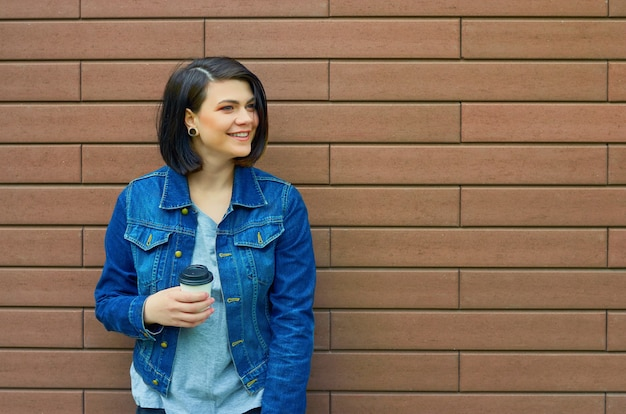 갈색 벽돌 벽에 거리에 그녀의 손에 커피 한잔과 함께 젊은 웃는 소녀