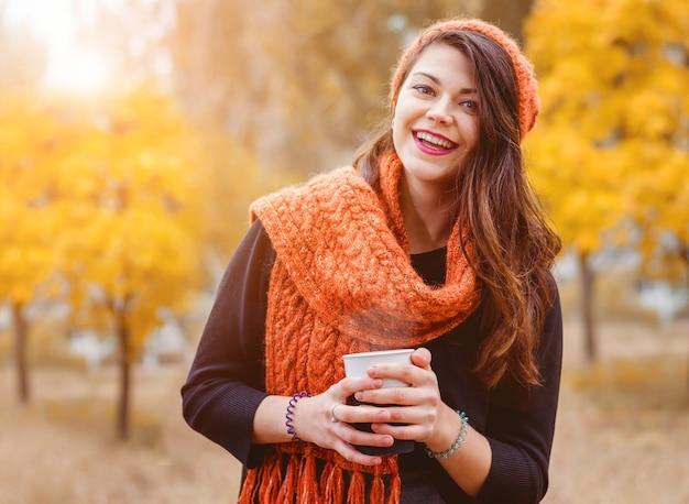 屋外の公園を散歩するためにコーヒー(お茶)を持って笑っている少女。秋の天気。太陽光線がモデルを後ろから照らします。