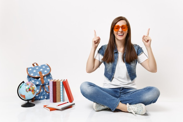 Young laughing happy woman student with closed eyes in red heart glasses pointing index fingers up near globe backpack books isolated