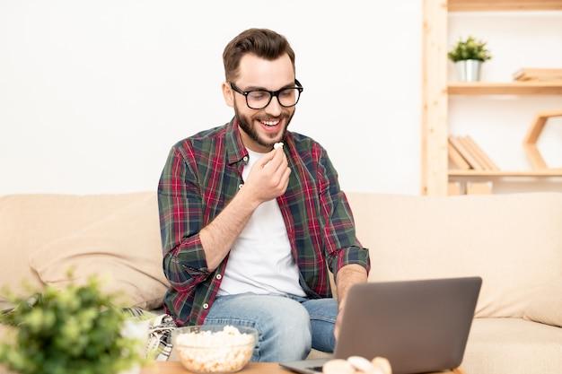 ノートパソコンで映画を見ながらポップコーンとお茶を飲んで笑っている若者