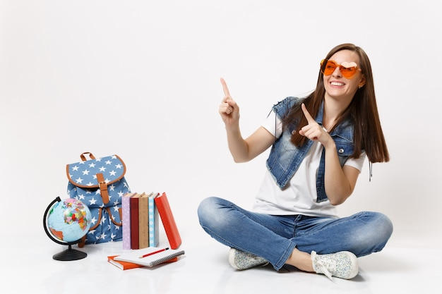 Молодая смеющаяся радостная студентка в очках с красным сердцем, указывая указательными пальцами в сторону, сидит возле земного шара, рюкзака, школьных учебников, изолированных на белой стене